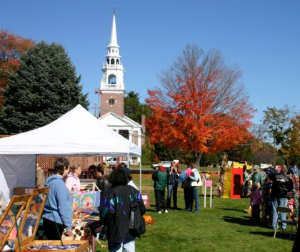 Outdoor fall fair with tents in front of church steeple