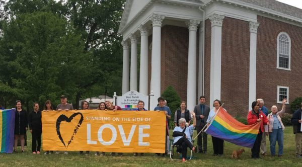 People holding love and rainbow banners
