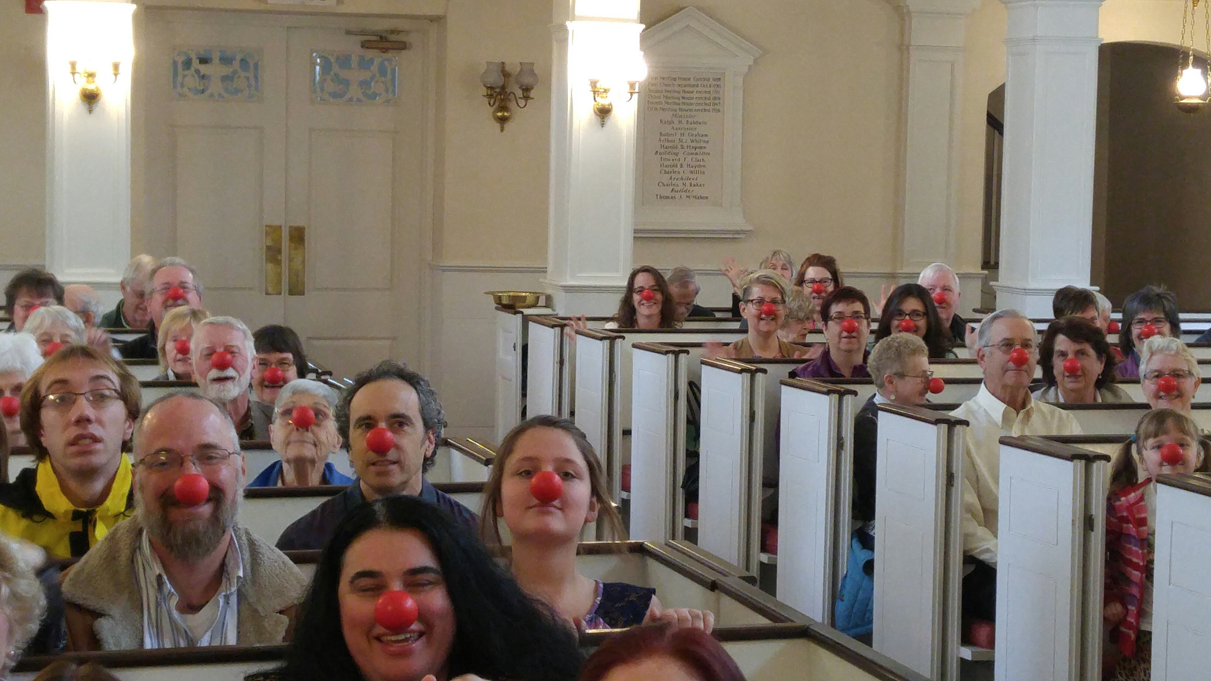 Congregation in pes, wearing red noses.