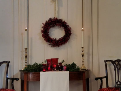 chancel decorate with wreath, greens and red vases