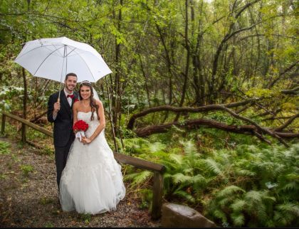 Bride and groom in woodland garden, with umbrella