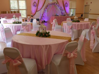 round tables covered with pink tables cloths, chairs covered in white cloth with pink bows, lantern center pieces